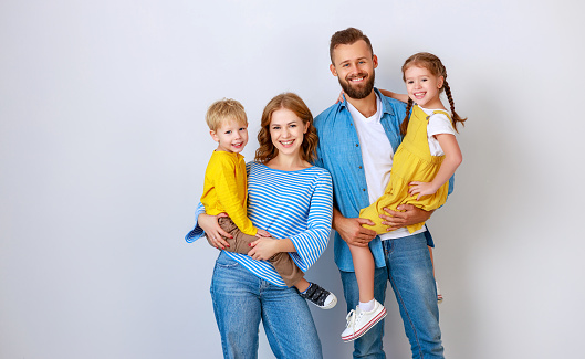 921362094 istock photo happy family mother father and children daughter and son  near an   grey blank wall 1182457252
