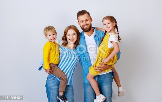 921362094istockphoto happy family mother father and children daughter and son  near an   grey blank wall 1184406404