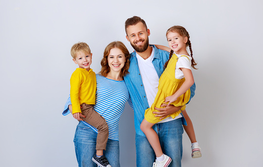 921362094 istock photo happy family mother father and children daughter and son  near an   grey blank wall 1184406404