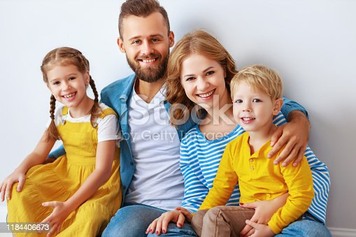 921362094istockphoto happy family mother father and children daughter and son  near an   grey blank wall 1184406673
