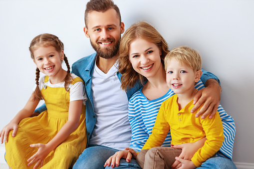 921362094 istock photo happy family mother father and children daughter and son  near an   grey blank wall 1184406673
