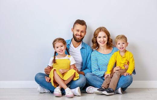 921362094 istock photo happy family mother father and children daughter and son  near an   grey blank wall 1184407314
