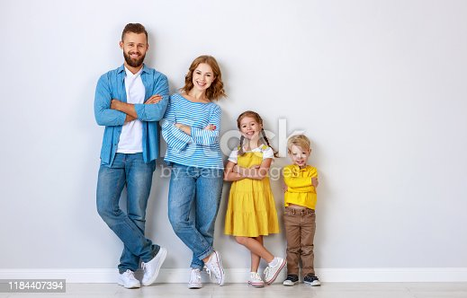921362094istockphoto happy family mother father and children daughter and son  near an   grey blank wall 1184407394