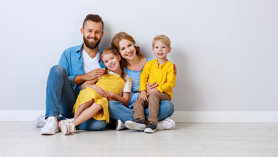 921362094 istock photo happy family mother father and children daughter and son  near an empty   blank wall 1202693212