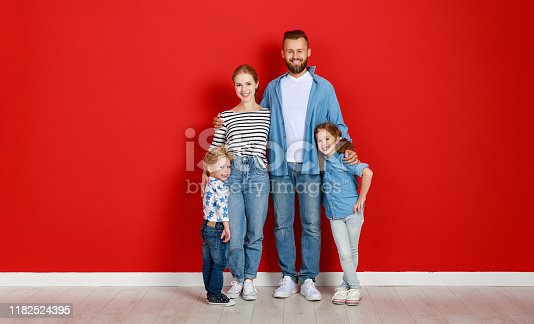921362094istockphoto happy family mother father and children daughter and son  near an   red wall 1182524395
