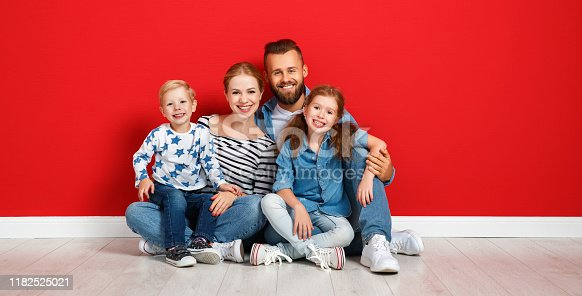 921362094istockphoto happy family mother father and children daughter and son  near an   red wall 1182525021