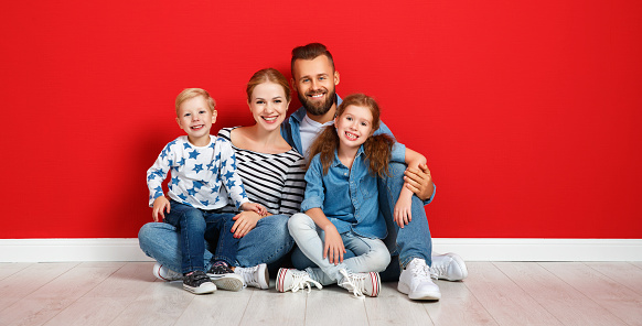 921362094 istock photo happy family mother father and children daughter and son  near an   red wall 1182525021