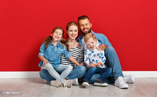 921362094istockphoto happy family mother father and children daughter and son  near an   red wall 1183730127