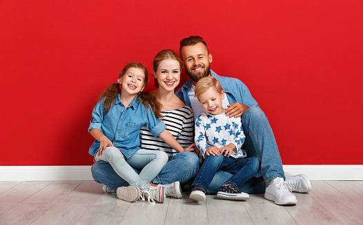 921362094 istock photo happy family mother father and children daughter and son  near an   red wall 1183730127