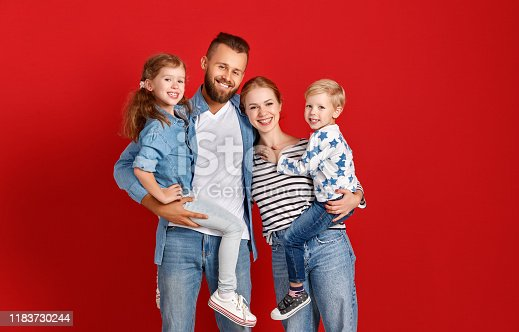 921362094istockphoto happy family mother father and children daughter and son  near an   red wall 1183730244