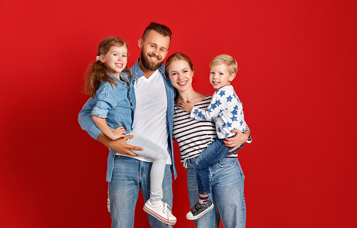 921362094 istock photo happy family mother father and children daughter and son  near an   red wall 1183730244