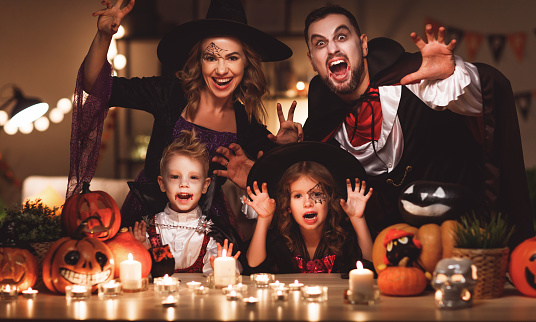 happy family mother father and children in costumes and makeup on a celebration of Halloween in dark home
