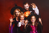 istock happy family mother father and children in costumes and makeup on  Halloween on dark red background 1177921689