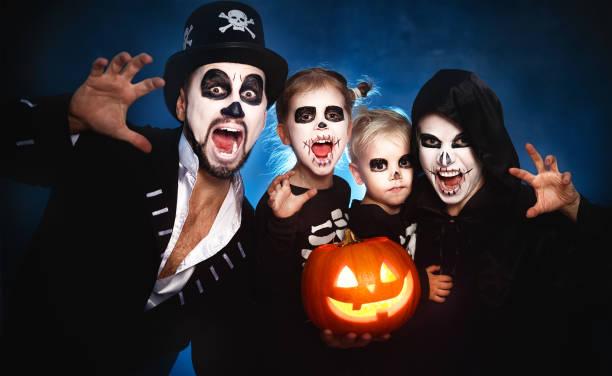 glückliche familie mutter vater und kinder kostüme und make-up auf halloween - halloween party lebensmittel stock-fotos und bilder
