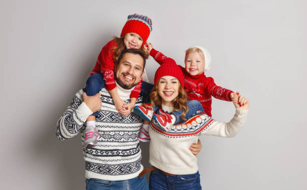 happy family mother, father and children in knitted hats and sweaters on gray background - christmas background стоковые фото и изображения