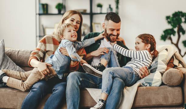 felice famiglia madre padre e figli a casa sul divano - family foto e immagini stock