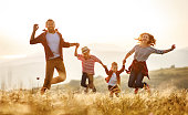 istock Happy family: mother, father, children son and daughter jumping on sunset 1199082028