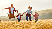 istock Happy family: mother, father, children son and daughter jumping on sunset 1204279050