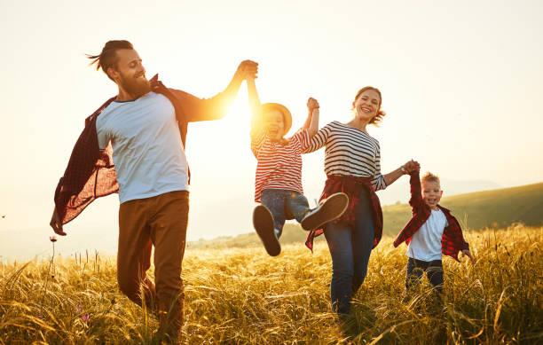 Glückliche Familie: Mutter, Vater, Sohn und Tochter auf Sonnen – Foto