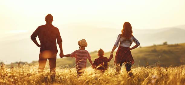 Glückliche Familie: Mutter, Vater, Sohn und Tochter bei Sonnenuntergang – Foto
