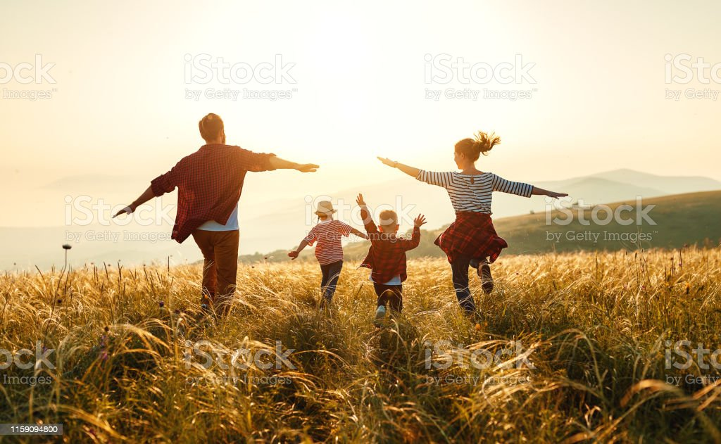 Gelukkige familie: moeder, vader, kinderen zoon en dochter op zonsondergang - Royalty-free Broer Stockfoto
