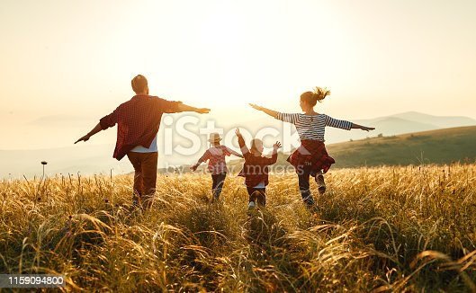 istock Happy family: mother, father, children son and daughter on sunset 1159094800