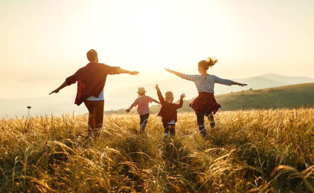 幸福的家庭:母親、父親、孩子、兒子和女兒在日落時分 - 幸福 個照片及圖片檔