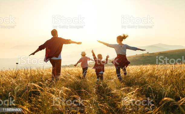 Happy Family Mother Father Children Son And Daughter On Sunset Stock Photo - Download Image Now