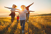 istock Happy family: mother, father, children son and daughter on sunset 996495748