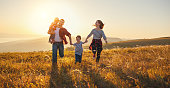 istock Happy family: mother, father, children son and daughter on sunset 996495800