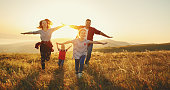 istock Happy family: mother, father, children son and daughter on sunset 996495858