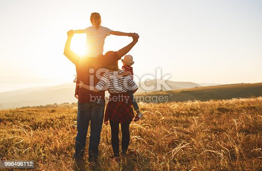 istock Happy family: mother, father, children son and daughter on sunset 996496112