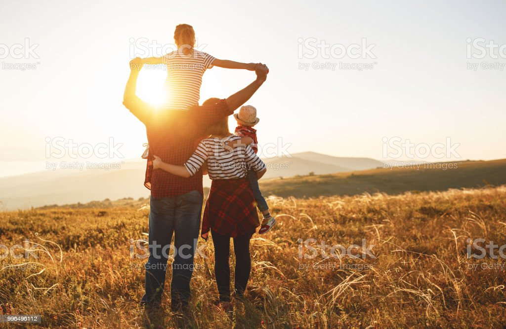 Happy family: mother, father, children son and daughter on sunset стоковое фото