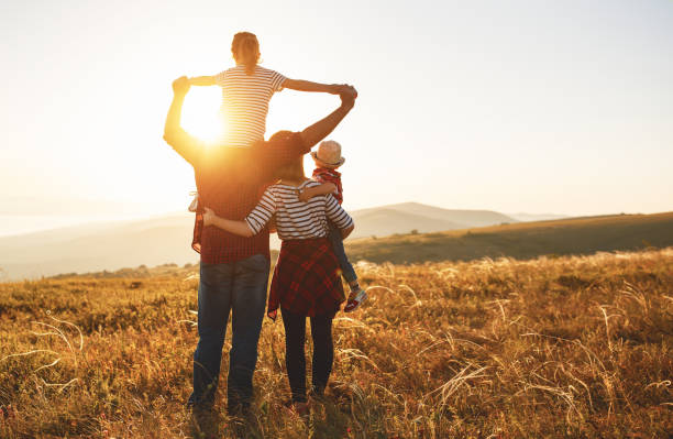 happy family: mother, father, children son and daughter on sunset - family vacation stock photos and pictures
