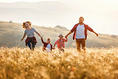 istock Happy family: mother, father, children son and daughter runing and jumping on sunset 1205460641