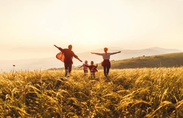 幸福的家庭:母親、父親、孩子、兒子和女兒在夕陽下奔跑和跳躍 - 幸福 個照片及圖片檔