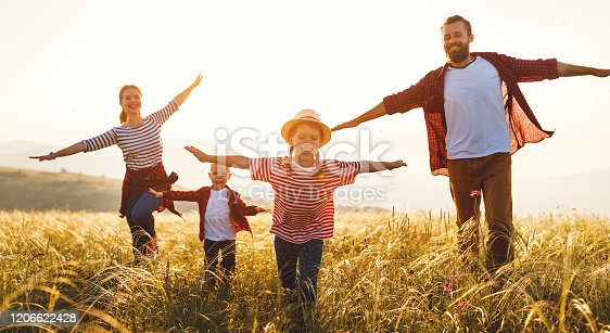 Happy family: mother, father, children son and  daughter runing and jumping on nature  on sunset
