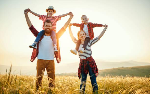 szczęśliwa rodzina: matka, ojciec, dzieci syn i córka stojące i przytulające się na zachodzie słońca - four seasons zdjęcia i obrazy z banku zdjęć