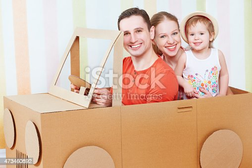496487362 istock photo Happy family mother, father, daughter ride on toy car 473460892