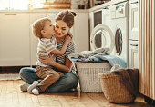 Happy family mother housewife and child son in laundry with washing machine
