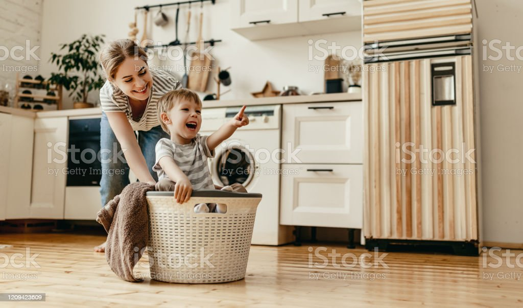 Happy family mother housewife and child   in laundry with washing machine - Royalty-free Adult Stock Photo
