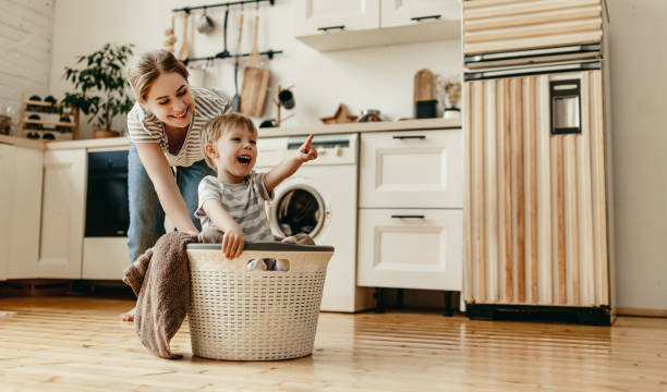 happy family mother housewife and child   in laundry with washing machine - casa imagens e fotografias de stock