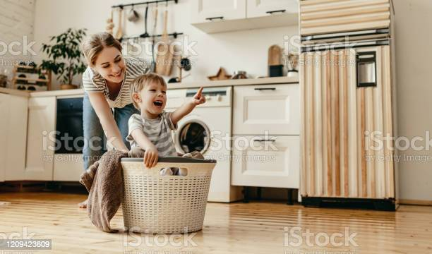 Happy Family Mother Housewife And Child In Laundry With Washing Machine - Fotografias de stock e mais imagens de Adulto