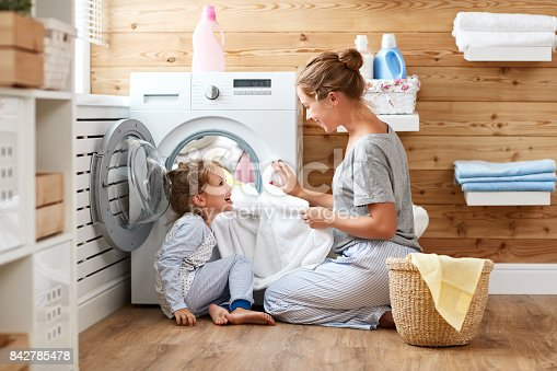 istock Happy family mother housewife and child   in laundry with washing machine 842785478