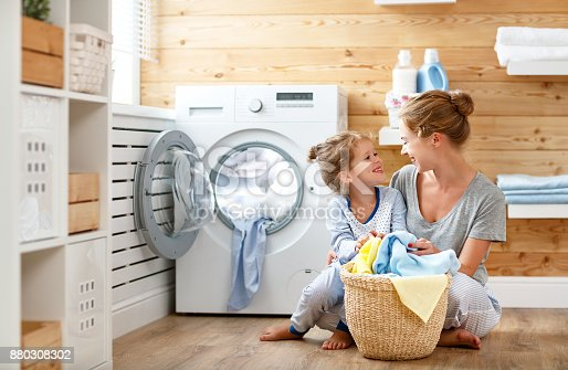 istock Happy family mother housewife and child   in laundry with washing machine 880308302