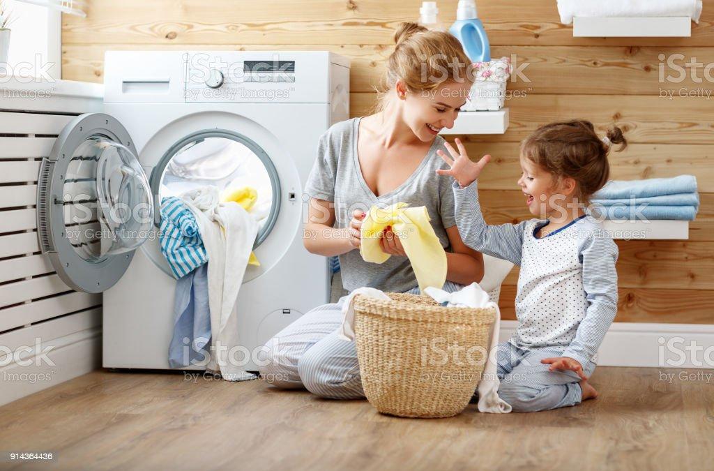 Femme au foyer mère de famille heureuse et l'enfant dans la buanderie avec machine à laver - Photo