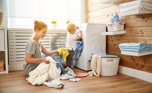 dona de casa feliz mãe de família e crianças na máquina de lavar roupa carga - dona de casa - fotografias e filmes do acervo