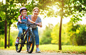istock happy family mother teaches child daughter to ride a bike in the Park 1173722330