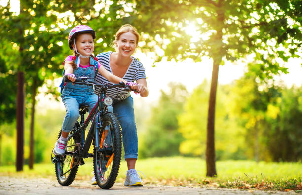 happy family mother teaches child daughter to ride a bike in the park - montare foto e immagini stock