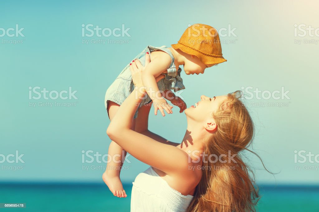 happy family mother with baby son walks by ocean on beach in summer stock photo
